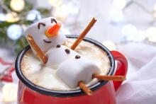 snowman made out of marshmellows in a mug of hot chocolate