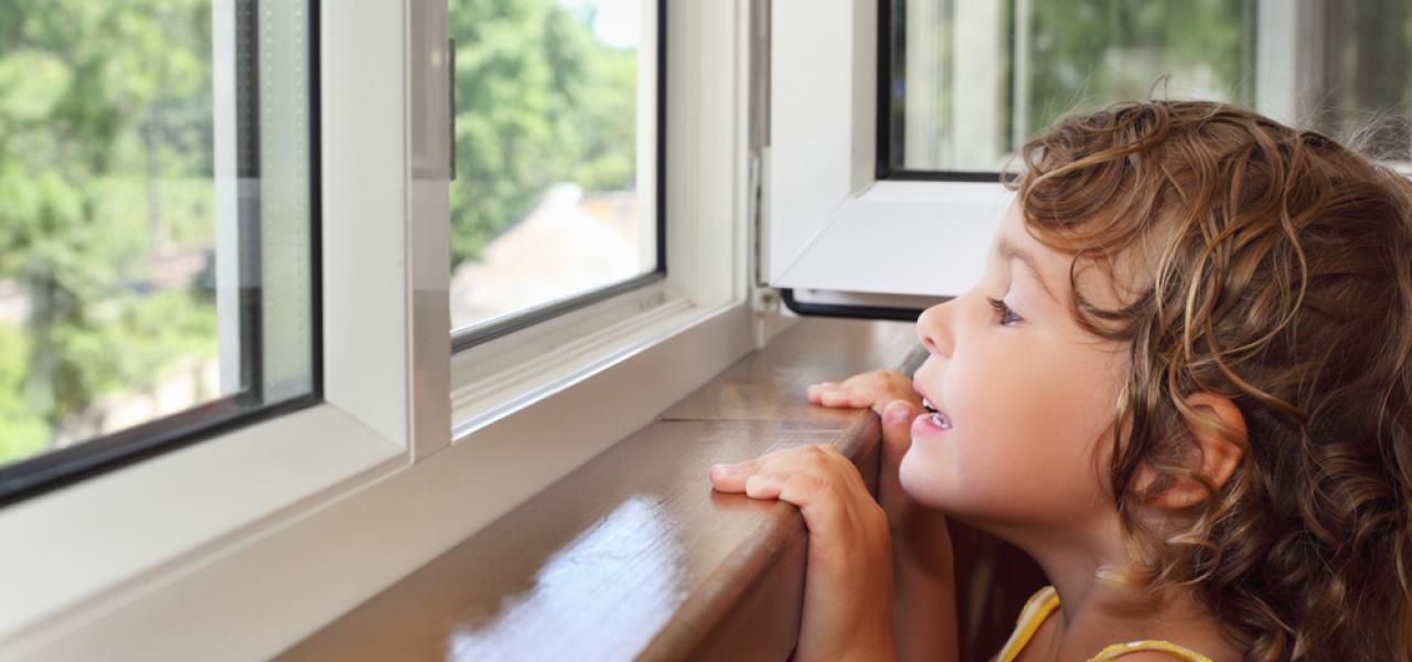 young child looking over the edge of windowsill out open window springtime