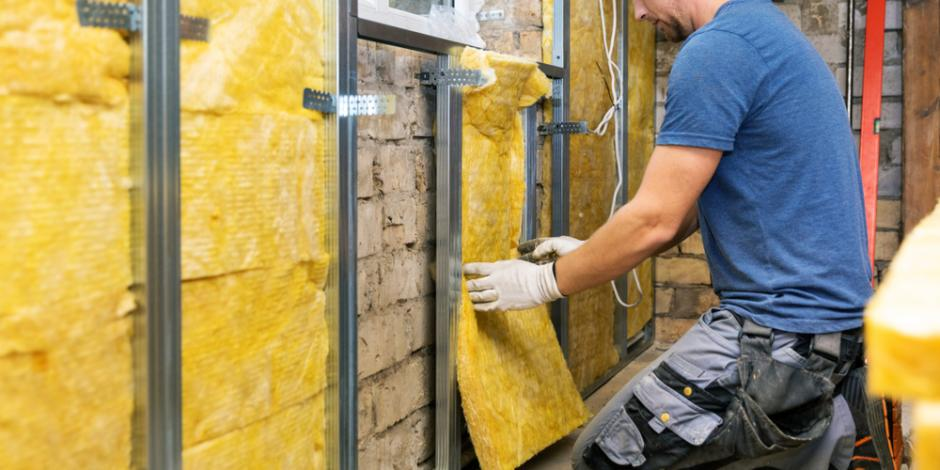 technician installing insulation in basement