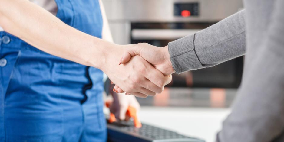 friendly home technician shaking hands with homeowner